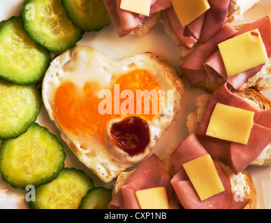 Fried egg on heart - shaped toast with cucumber and ham for Valentine's Day - Stock Photo