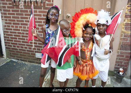 USA: Brooklyn, NY. Costumed children carrying the flags of Trinidad and Tobago await the start of The Caribbean - Stock Photo