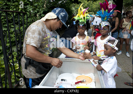 USA: Brooklyn, NY. Costumed children buy ices during Caribbean Kiddies Day Parade, Crown Heights, 2012. - Stock Photo