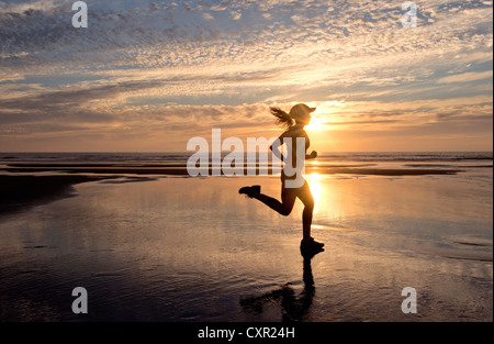 Woman running on beach at sunrise - Stock Photo