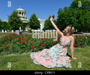 Young woman holding a rose, bed of roses, building of the Kuenstlerbund association at the back, Schlosspark garden, - Stock Photo
