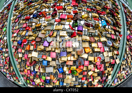 Padlocks, love locks, on a security fence separating the footpath from the railway tracks at the Hohenzollern Bridge, - Stock Photo