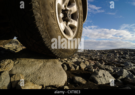 Tire, cross country vehicle on a rural road through a lava field, Highlands of Iceland, Iceland, Europe - Stock Photo