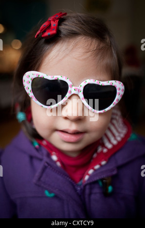 Portrait of young girl wearing heart shaped sunglasses - Stockfoto