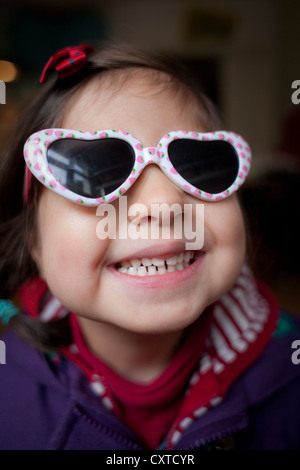 Portrait of young girl wearing heart shaped sunglasses, smiling - Stockfoto