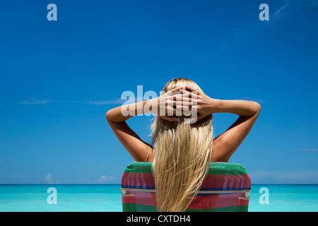 Woman relaxing in lawn chair on beach - Stock Photo