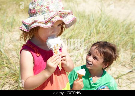 Children eating ice cream on beach - Stock Photo