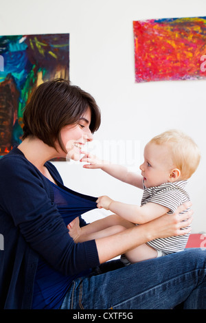 Mother playing with baby in living room - Stock Photo