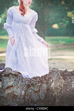 Faceless young brunette woman in a beautiful white wedding gown, standing on a romantic bridge outdoors - Stock Photo