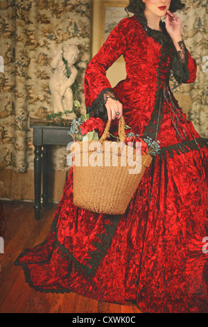 Cropped mysterious shot of a girl with short black hair and red lipstick wearing a fancy red historical gown - Stock Photo