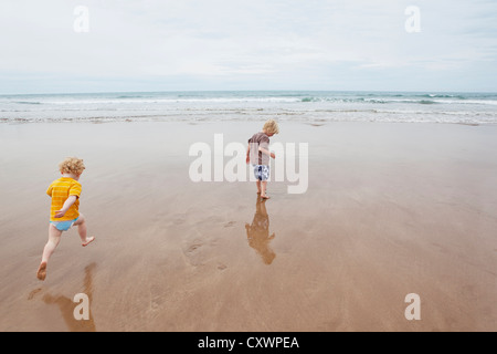 Children playing in waves on beach - Stock Photo