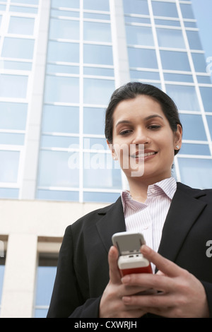 Businesswoman using cell phone outdoors - Stockfoto