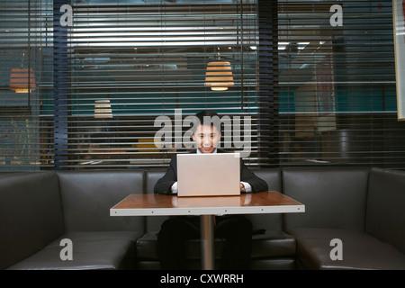 Businessman using laptop in cafe - Stockfoto