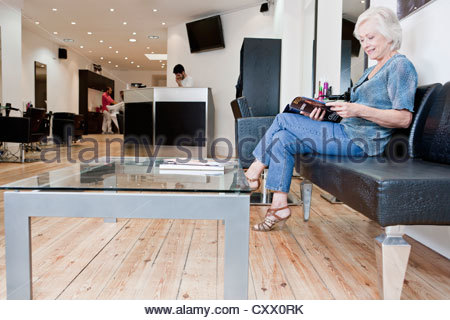 A senior woman reading a magazine at a hairdressers - Stock Photo