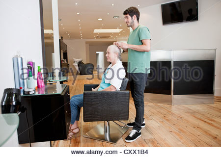 hair stylist at work - hairdresser applying a color on ...