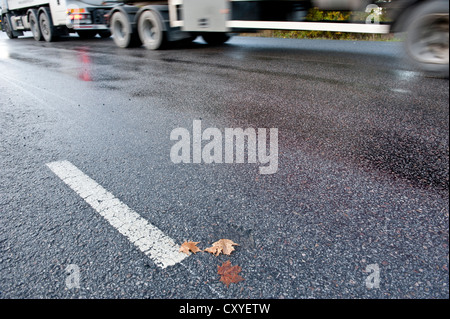 Truck driving on treacherous and slippery road due to rain or frost - Stock Photo