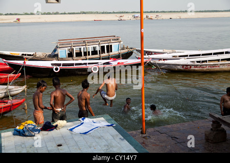 Young Men jumping into the River Ganges in Varanasi, India - Stock Photo