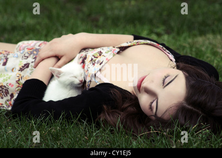 Young woman with dark hair sleeping in grass holding a white kitten - Stock Photo