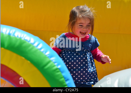 Happy child girl jumps on a children's bouncy castle inflatable jumper playground. - Stock Photo