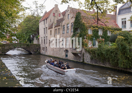 Tourists enjoying a boat trip on a beautiful canal in the Belgian city of Brugge - Stock Photo