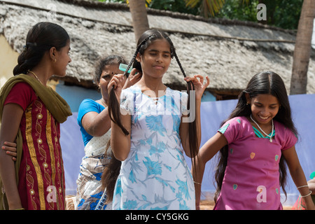 Indian Mother brushing and plaiting daughters hair for Dasara Festival in a rural indian village. Andhra Pradesh, - Stock Photo