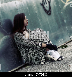 a woman is sitting on a street, leaning against a graffiti wall - Stock Photo