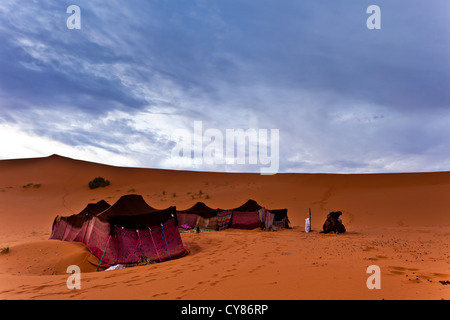 Colorful Bedouin nomad tent camp at an oasis in the Sahara Desert  and dramatic cloudy sky in Morocco - Stock Photo