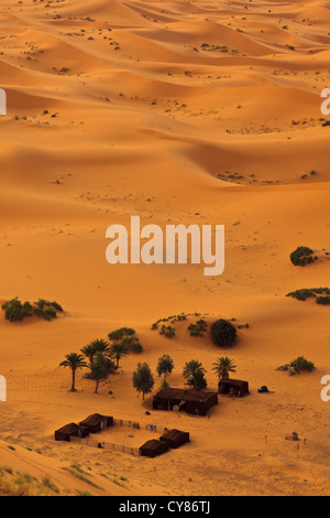 Aerial view of Sahara desert sand dunes and Bedouin camp, in an oasis in Morocco - Stock Photo