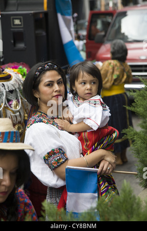 Hispanic Day Parade, New York City. Woman in traditional Guatemalan folk dress with child. - Stock Photo