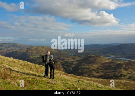 Two walkers on Silver How, looking towards the lakes of Elterwater and Windermere, Lake District National Park, - Stock Photo