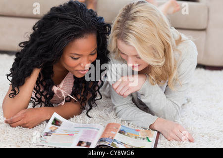 Two women lying on the floor are reading a magazine - Stock Photo