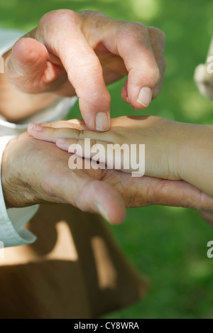 Elderly person holding child's hand, cropped - Stockfoto