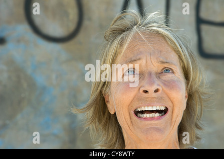 Senior woman looking up with fearful expression on face - Stock Photo