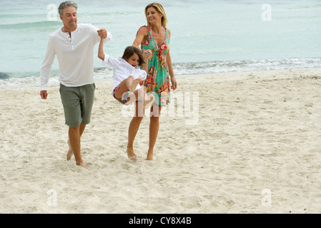Parents swinging young daughter as they walk on beach - Stock Photo