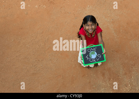 Indian village girl with ONE WORLD written on a chalkboard in a rural indian village. Andhra Pradesh, India. Copy - Stock Photo
