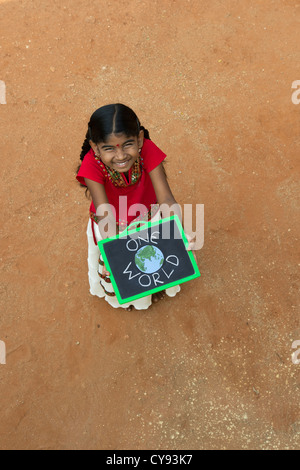 Indian village girl with ONE WORLD written on a chalkboard in a rural indian village. Andhra Pradesh, India - Stock Photo