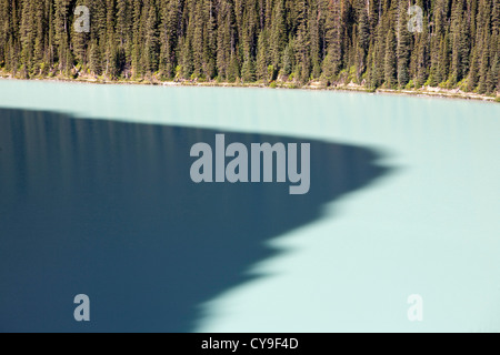 A mountain peak casts a large shadow on Lake Louise in the Canadian Rockies. - Stock Photo