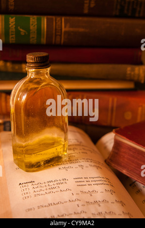 Mysterious old bottle sitting on desk of old books with one open to the chemical formula for Arsenic. - Stock Photo