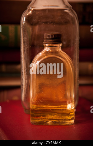 Mysterious old bottles sitting on a stack of old books. - Stock Photo