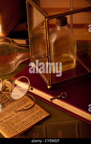 Mysterious old bottle sitting on a desk with old books. - Stock Photo