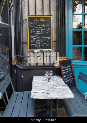Chalkboard above tables and benches at an outdoor cafe in Paris - Stock Photo