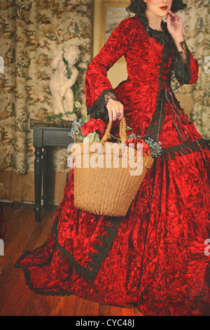 Cropped mysterious shot of a girl with short black hair and red lipstick wearing a fancy red historical gown - Stockfoto