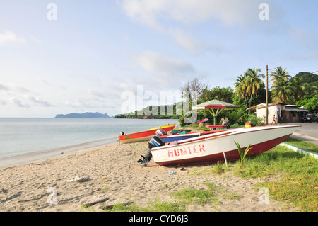 Blue sky view, to Union Island, four white red painted fishing boats on beach sand by road, Hillsborough, Carriacou, - Stockfoto