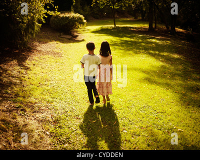 Golden hour: boy and girl summer afternoon walk in woods - Stock Photo