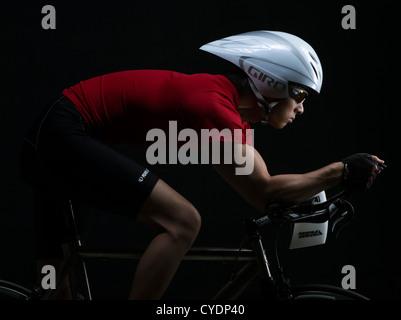 triathlete  / time trial racer on bicycle wearing aero helmet - Stock Photo