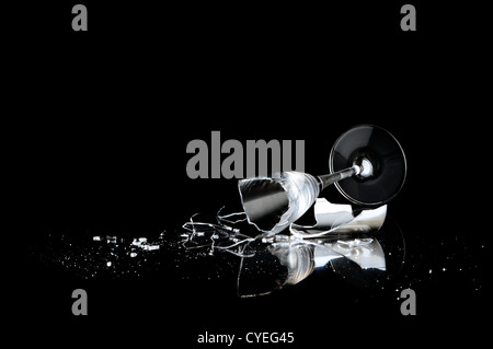 elegant wine glass broken on a dark background - Stock Photo