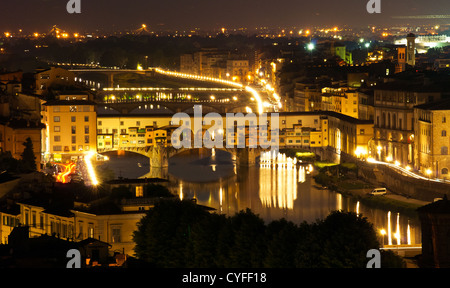 Night view over Florence, in Italy with Ponte Vecchio (a bridge over Arno river)in front - Stock Photo