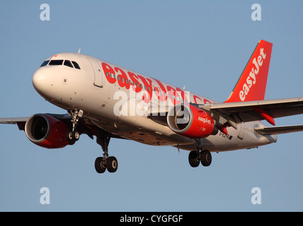 easyJet Airbus A319 on final approach at sunset - Stock Photo