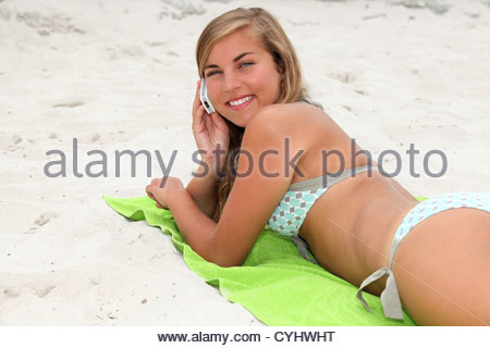 portrait of a young woman on the beach with phone - Stockfoto