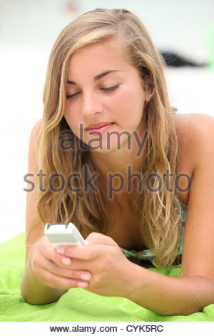 Teenage girl texting on the beach - Stock Photo
